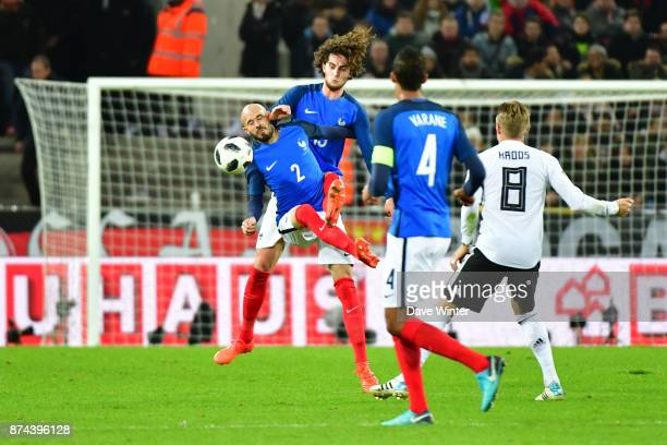 Christophe Jallet of France and Adrian Rabiot of France collide whilst going for the same ball during the international friendly match between...