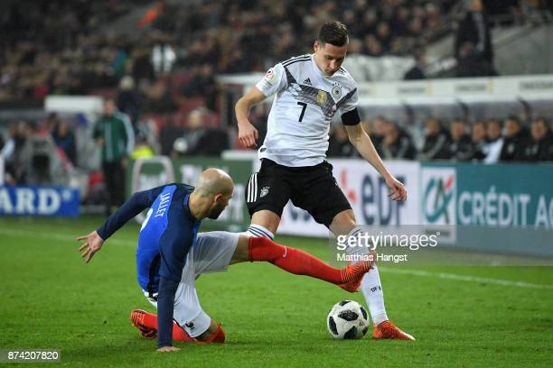 Christophe Jallet of France tackles Julian Draxler of Germany battle for possession during the international friendly match between Germany and...