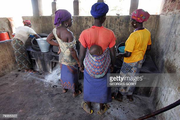 Christophe PARAYRE Burkinabe women from the Ragussi association gather 14 January 2008 around cauldrons used to process shea nuts at the organic shea...