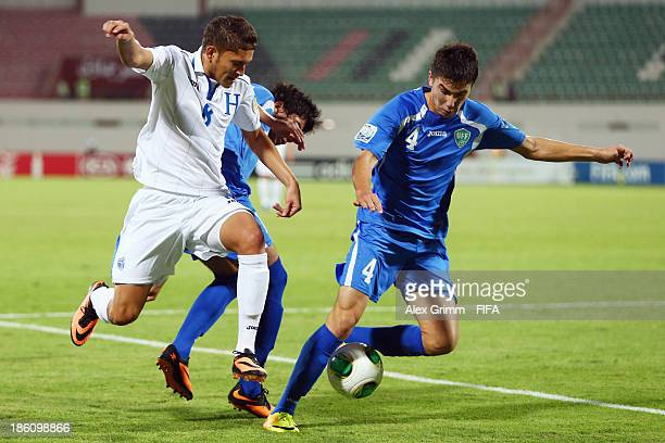 Christopher Alegria 8l9 of Honduras is challenged by Akramjon Komilov of Uzbekistan during the FIFA U17 World Cup UAE 2013 Round of 16 match between...