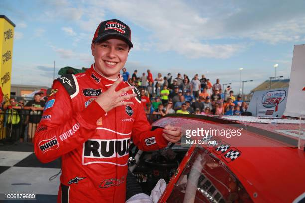 Christopher Bell driver of the Ruud Toyota poses with the winner's sticker Victory Lane after the NASCAR Xfinity Series US Cellular 250 presented by...