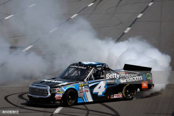 Christopher Bell driver of the SiriusXM Toyota celebrates with a burnout after winning the NASCAR Camping World Truck Series Overton's 150 at Pocono...