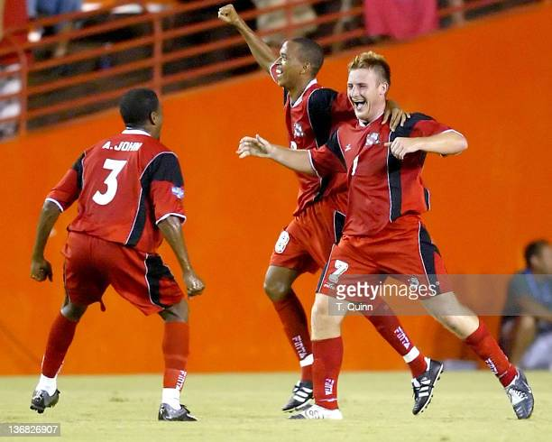 Christopher Birchell celebrates his goal with Emery John and Dennis Lawrence during a match at the Orange Bowl Miami Florida July 7 2005 The game...