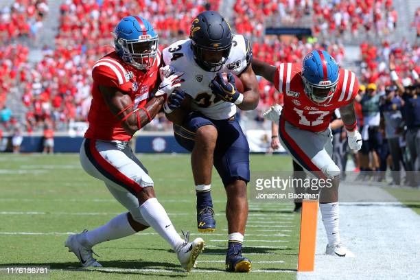 Christopher Brown Jr #34 of the California Golden Bears rushes for a touchdown as Willie Hibbler of the Mississippi Rebels and Jon Haynes defend...