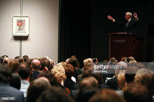 Christopher Burge auctioneer and honorary chairman of Christie's right acknowledges a bid for Andy Warhol's painting entitled Small Torn Campbell's...
