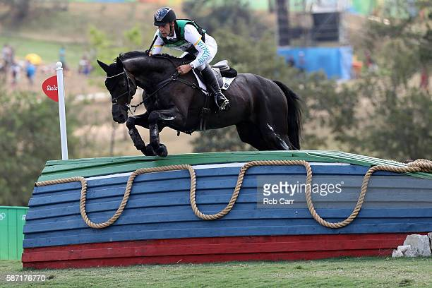 Christopher Burton of Australia riding Santano II clears a jump during the Cross Country Eventing on Day 3 of the Rio 2016 Olympic Games at the...