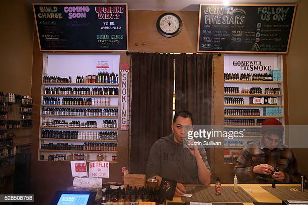 Christopher Chin blows puffs on an ecigarette as he waits for customers at Gone With the Smoke Vapor Lounge on May 5 2016 in San Francisco California...