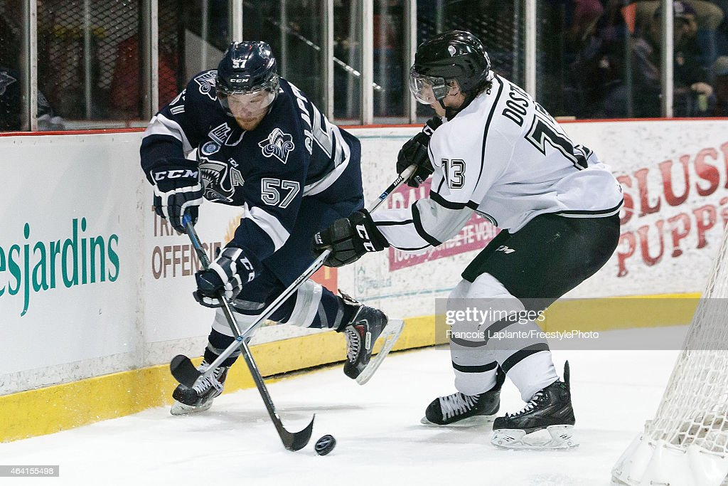 Christopher Clapperton #57 of the Rimouski Oceanic battles for the puck against Alex Dostie #13 of the Gatineau Olympiques on February 22, 2015 at Robert Guertin Arena in Gatineau, Quebec, Canada.