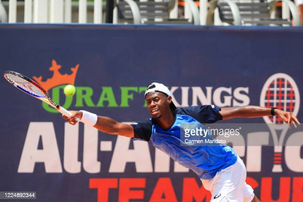 Christopher Eubanks of the United States returns the ball against John Isner of the United States during the final day of the DraftKings All-American...