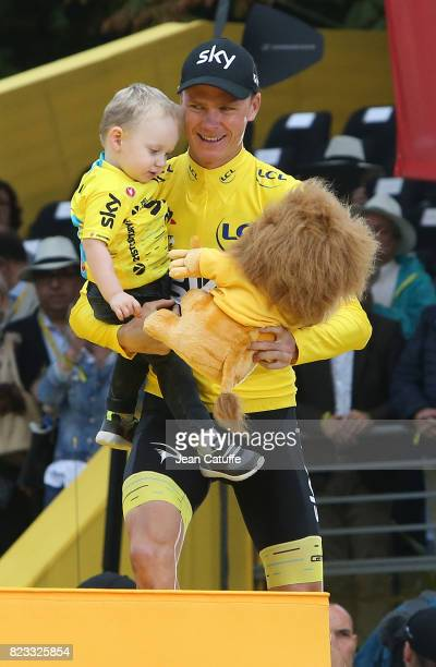 Christopher Froome of Great Britain and Team Sky holds his son Kellan Froome during the trophy ceremony following stage 21 of the Tour de France 2017...