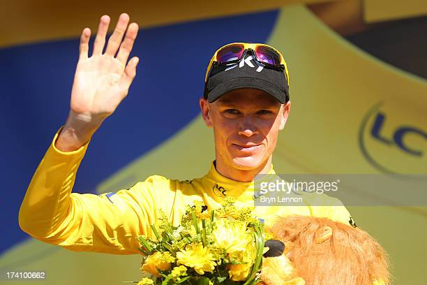 Christopher Froome of Great Britain and Team Sky Procycling celebrates on the podium as he secures the leader's yellow jersey after stage twenty of...