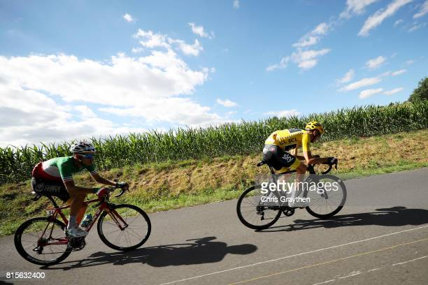 Christopher Froome of Great Britain riding for Team Sky in the leader's jersey and Fabio Aru of Italy riding for Astana Pro Team ride in the peloton...