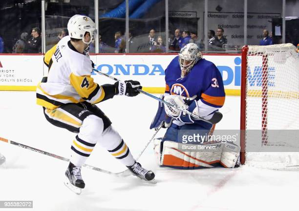 Christopher Gibson of the New York Islanders makes the first period save on Justin Schultz of the Pittsburgh Penguins at the Barclays Center on March...