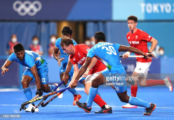 Christopher Griffiths of Team Great Britain runs with the ball whilst being challenged by Varun Kumar and Amit Rohidas of Team India during the Men's...