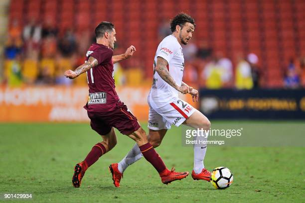 Christopher Herd of the Wanderers is tackled by Corey Gameiro of Brisbane during the round 14 ALeague match between the Brisbane Roar and the Western...