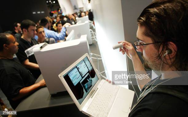 Christopher Jon uses a webcam to upload images on an inhouse wireless network to his website at the Macworld CreativePro show July 16 2003 in New...