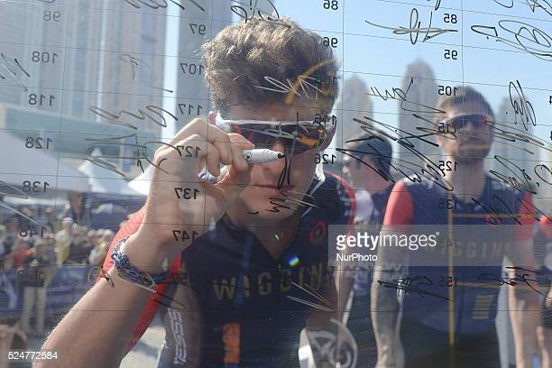 Christopher Latham signs watched by Bradley Wiggins riders from Team Wiggins ahead of the third stage of the 2016 Tour of Dubai the 172km The Westin...