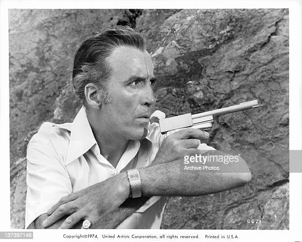 Christopher Lee along side a cliff wall pointing a gun in a scene from the film 'The Man With The Golden Gun' 1974