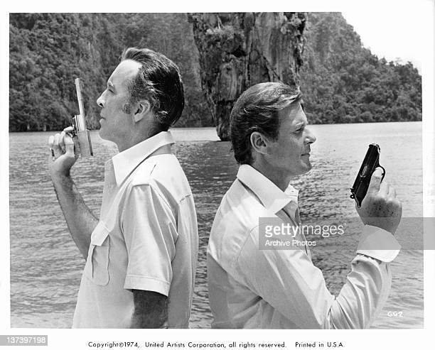 Christopher Lee back to back with Roger Moore each holding a gun in the air in a scene from the film 'The Man With The Golden Gun' 1974