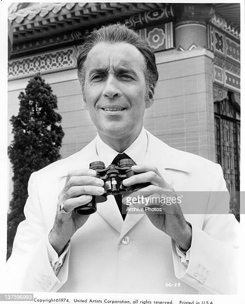 Christopher Lee holding binoculars with both hand and has a gold ring on each pinky finger in a scene from the film 'The Man With The Golden Gun' 1974