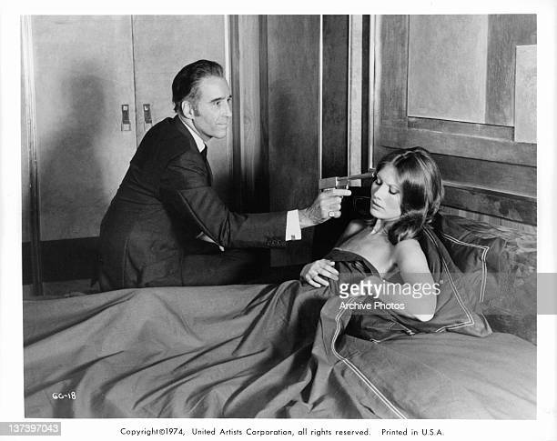 Christopher Lee holds a gun to Maud Adams head who is lying in bed in a scene from the film 'The Man With The Golden Gun' 1974