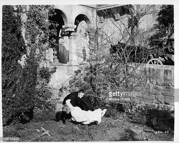 Christopher Lee hurls still another of his doomed victims into a living grave to await his blood lust in a scene from the film 'Horror of Dracula'...