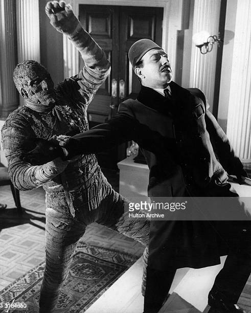 Christopher Lee in the role of Kharis the mummy attacking George Pastell playing Mehemet in a scene from the film 'The Mummy' directed by Terence...