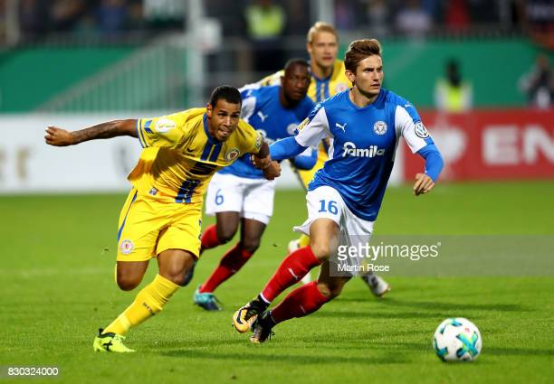 Christopher Lenz of Kiel and Onel Hernandez of Braunschweig battle for the ball during during the DFB Cup first round match between Holstein Kiel and...