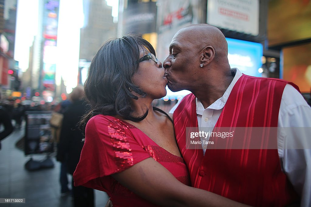 Christopher McVay (R) and Tamesha Leach kiss while posing in Times Square on Valentine's Day on February 14, 2013 in New York City. The pair live outside of the city in Yonkers, New York, and came to the city to celebrate the holiday.