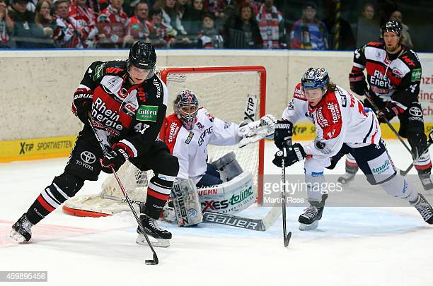 Christopher Minard of Koelner Haie and Jonas Mueller of Eisbaeren Berlin battle for the puck during the DEL Ice Hockey match between Koelner Haie and...