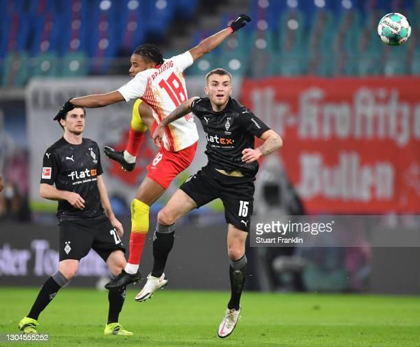 Christopher Nkunku of Leipzig is challenged by Louis Beyer of Gladbaduring the Bundesliga match between RB Leipzig and Borussia Moenchengladbach at...
