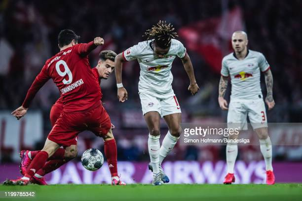 Christopher Nkunku of Leipzig is tackled by Philippe Coutinho and Robert Lewandowski of Muenchen during the Bundesliga match between FC Bayern...