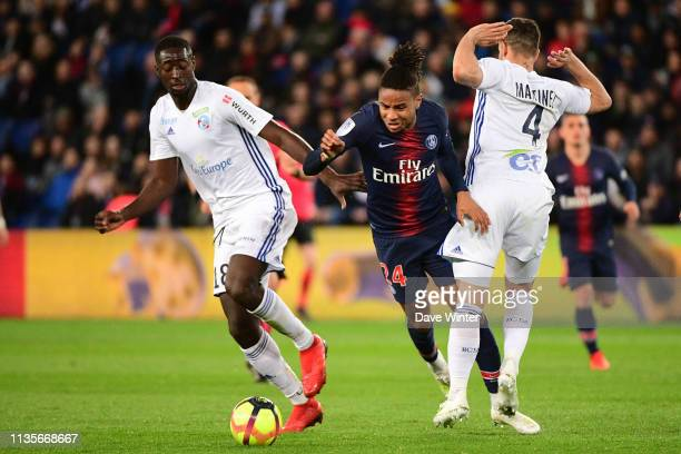 Christopher Nkunku of PSG tries to slip between Ibrahima Sissoko of Strasbourg and Pablo Martinez of Strasbourg during the Ligue 1 match between...