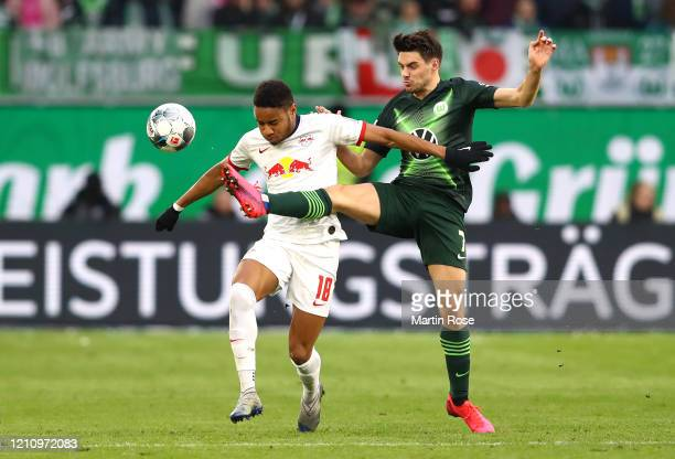 Christopher Nkunku of RB Leipzig battles for possession with Josip Brekalo of VfL Wolfsburg during the Bundesliga match between VfL Wolfsburg and RB...