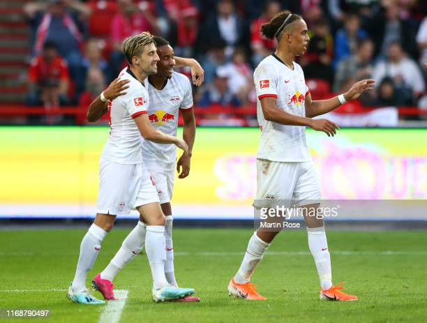 Christopher Nkunku of RB Leipzig celebrates after scoring his team's fourth goal with Kevin Kampl and Yussuf Poulsen during the Bundesliga match...