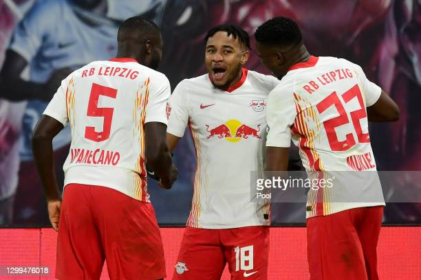 Christopher Nkunku of RB Leipzig celebrates after scoring their team's first goal with Dayot Upamecano and Nordi Mukiele during the Bundesliga match...