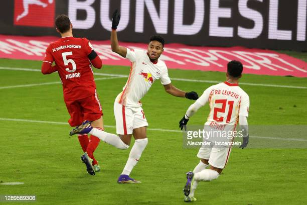 Christopher Nkunku of RB Leipzig celebrates with teammate Justin Kluivert after scoring his team's first goal during the Bundesliga match between FC...