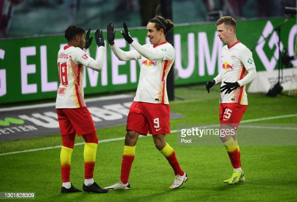 Christopher Nkunku of RB Leipzig celebrates with Yussuf Poulsen and Dani Olmo after scoring their team's second goal during the Bundesliga match...