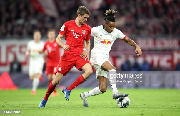 Christopher Nkunku of RB Leipzig is challenged by Thomas Muller of Bayern Munich during the Bundesliga match between FC Bayern Muenchen and RB...