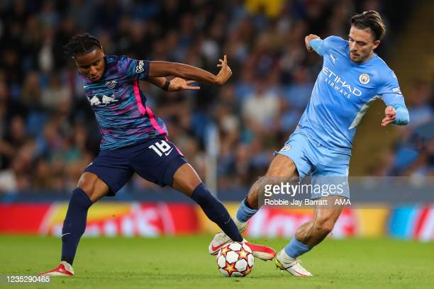 Christopher Nkunku of RB Leipzig tackles Jack Grealish of Manchester City during the UEFA Champions League group A match between Manchester City and...
