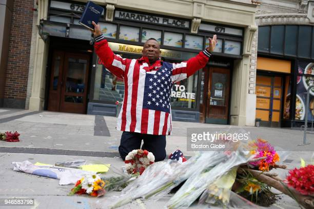 Christopher Nzenwa of Boston raises his hands in prayer as he kneels in front of a memorial at the site where one of the bombs went off on April 15...