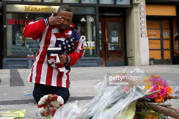 Christopher Nzenwa of Boston wipes away a tear after praying in front of a memorial at the site where one of the bombs went off on April 15 the five...