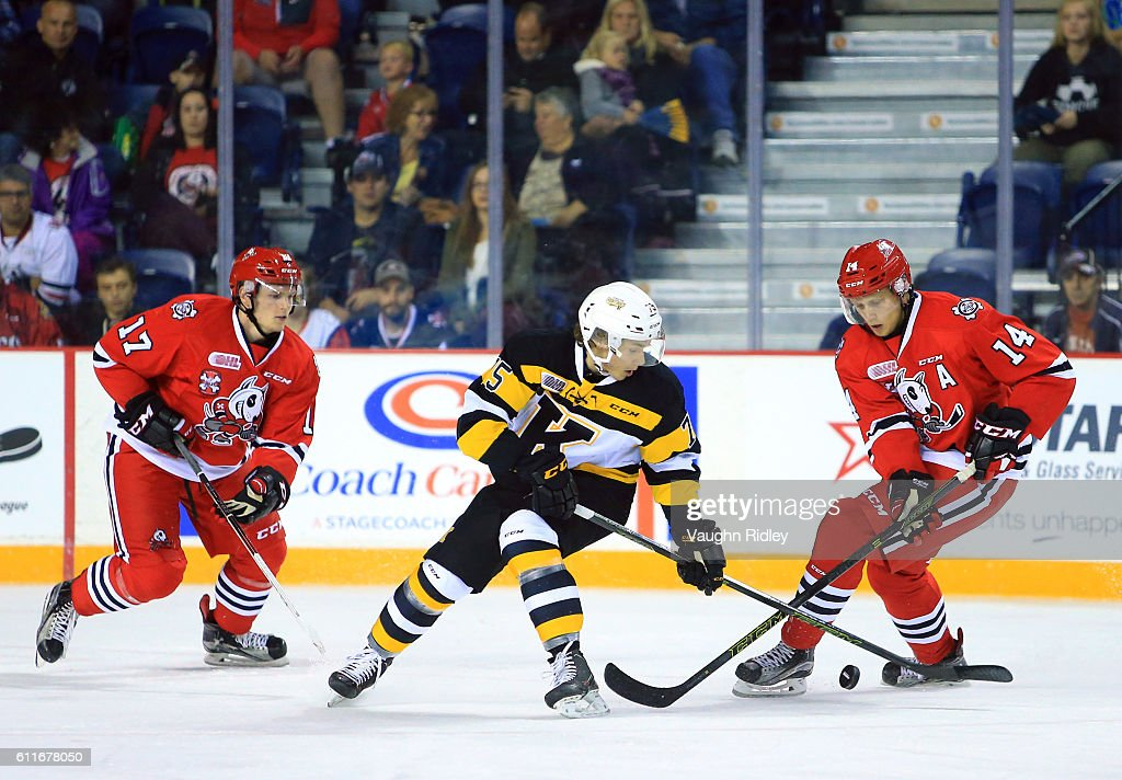 Christopher Paquette #14 of the Niagara IceDogs and Linus Nyman #75 of the Kingston Frontenacs battle for the puck during the first period of an OHL game at the Meridian Centre on September 30, 2016 in St Catharines, Ontario, Canada.