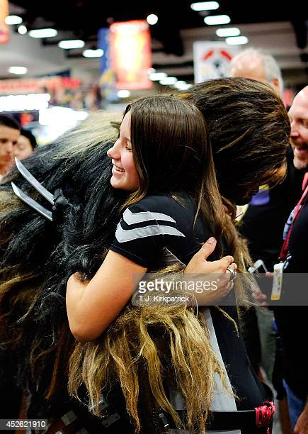 Christopher Petrone of San Diego CA towering over attendees in his handmade toscale Chewbacca costume bends down to hug a fan during the 45th annual...