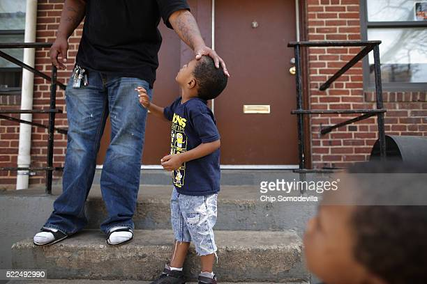 Christopher Pierce stands outside his apartment in the Gilmor Homes with two of his six children Chrisyrus and Chrixus both 3yearsold one year after...