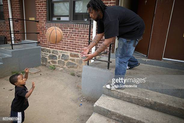 Christopher Pierce tosses a basketball with his son Chrisyrus outside their apartment in the Gilmor Homes one year after Freddie Gray died April 19...