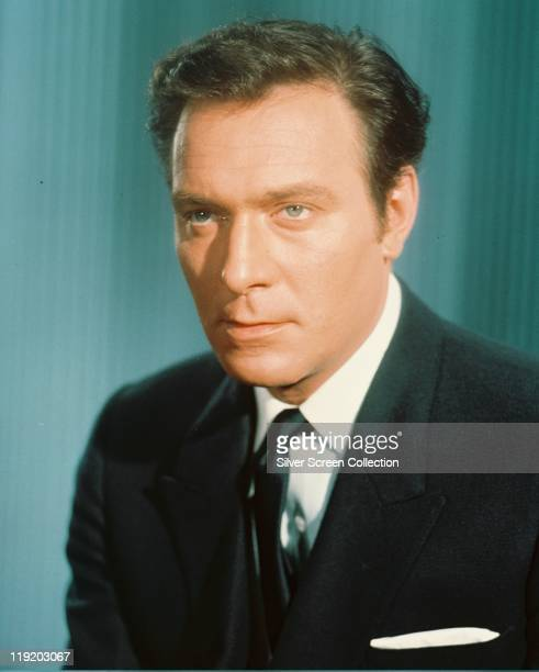 Christopher Plummer Canadian actor wearing a black jacket white shirt and black tie in a studio portrait against a blue background circa 1960