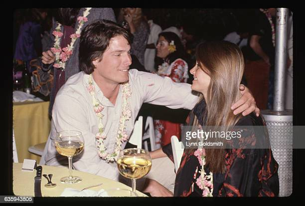 Christopher Reeve and Gae Exton gaze fondly at each other wearing leis as they sit at a table over glasses of wine