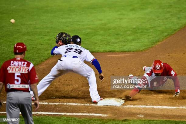 Christopher Roberson of Aguilas de Mexicali from Mexico slides safe to first base in a match against Tigres de Licey from the Dominican Republic...