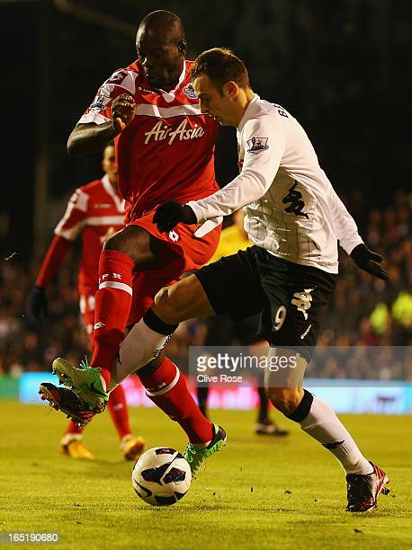Christopher Samba of Queens Park Rangers and Dimitar Berbatov of Fulham challenge for the ball during the Barclays Premier League match between...